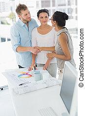 Interior designer shaking hands with happy client