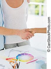 Interior designer shaking the hand of customer