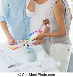 Interior designer showing colour wheel to client in her...