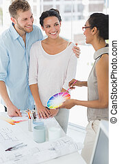 Interior designer showing colour wheel to happy clients in...