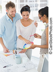 Interior designer showing colour wheel to smiling clients in...