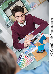 interior designer showing colour wheel to customer in his studio