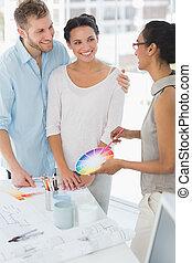 Interior designer showing colour wheel to happy clients