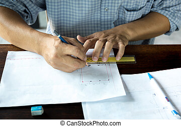 Interior designer works on a hand sketch using pencils and rule on the desk