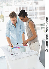 Interior designers looking at colour wheel and blueprints