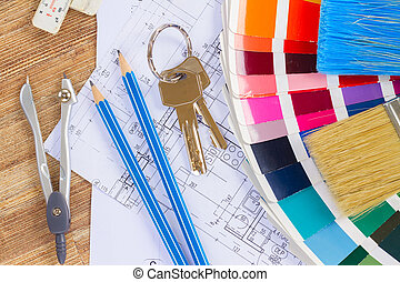 Interior designer's working table with architectural plan of the house, keys, color palette and brushes
