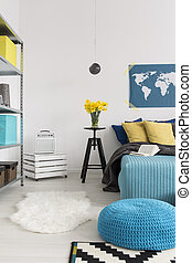 Cozy bedroom with large bed, decorative pillows and blue pouffe, light walls