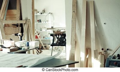 Interior of a carpenter workroom. Work tools, wood planks...