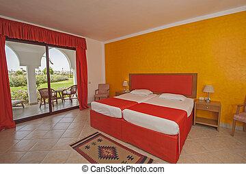 Interior of a luxury hotel bedroom with balcony