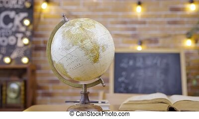 Interior of a modern empty classroom with globe, chalkboard, desk and textbook. School, home education, distance learning. Studying in primary grades, first lesson, school knowledge. Schooling of geography in elementary school. Close up.