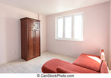 Interior of a non-residential room empty for sale with several pieces of furniture