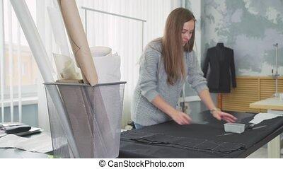 Interior of a sewing workshop. Female designer working in her workshop