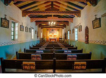 inside view of the small chapel in the historic California Mission San Carlos Borromeo del Rio Carmelo or Carmel Mission