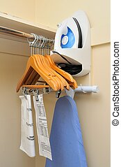 Interior of clothes rack with hangers and iron equipment.