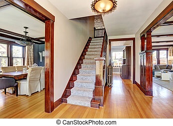 Interior of hallway with staircase and hardwood floor.