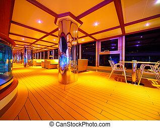 Interior of illuminated restaurant on the cruise ship deck at night