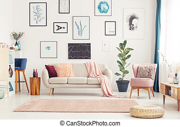 Interior of a pink living room with white couch, pink armchair and posters on the wall