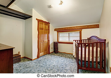 Interior of nursery room with baby crib in log cabin house.