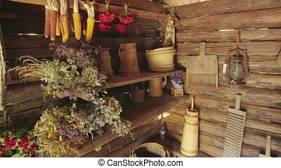 Agricultural products hang to dry alongside obsolete tools, inside this wooden storage shed on a rural, Ukrainian farm. FullHD stock video