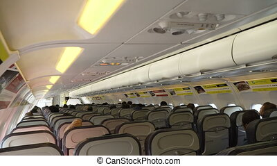 Interior of large passengers airplane with people on seats. Aircraft cabin with rows of seats. Travel concept. 4K video.