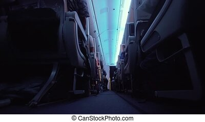Interior passengers airplane with people on seats. Aircraft cabin with rows of seats. Passengers traveling by a modern commercial plane, inside of an airplane. Travel concept. 4K video.