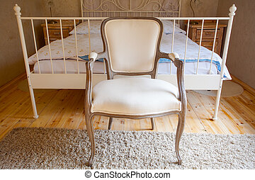 Interior of vintage bedroom. Bed and retro chair.