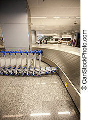 photo of row of luggage trolleys and baggage claim line - ...