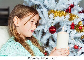 Interior portrait of a cute little girl at Christmas time, playing with a big candle