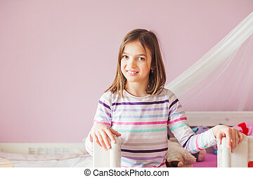 Interior portrait of a cute little girl in her room