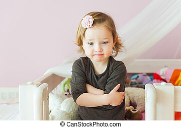 Interior portrait of a cute toddler girl in her room
