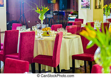 Interior restaurant with table, plates, glasses, cutlery and flower