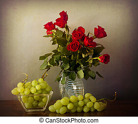 Interior retro with red roses on a glass vase, and grapes on a wooden table in chiaroscuro
