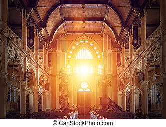 interior view of empty church with wooden bench decorated with flower bouquet, sunlight through church stained glass window