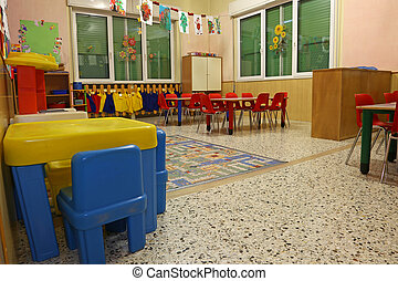 interiors of a nursery class with coloredchairs and drawings of children hanging on the walls