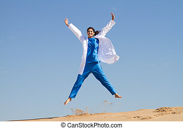 intern jumping on beach in scrubs