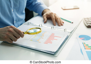 internal audit concept - man with magnifying glass inspecting business documents