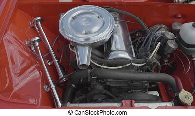 Internal combustion engine of a red car close-up.