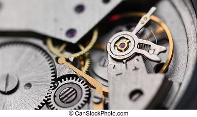 Internal working mechanism of the wristwatch with a rapidly rotating pendulum and gears. 4k clock close up with shallow depth of field.