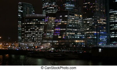 International business center, works 24 hours. High-rise building, office lights in the evening.