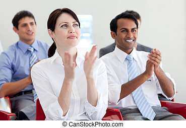 International business people clapping at a conference -...