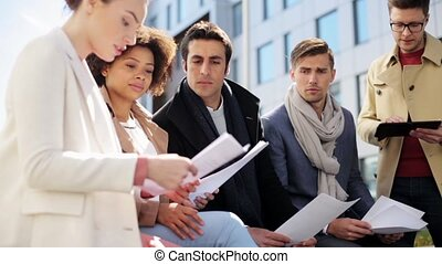 international business team with papers outdoors - business,...