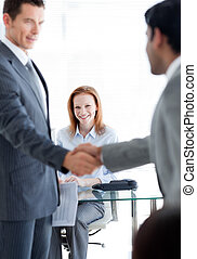International businessmen greeting each other at a job interview in an office