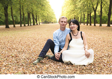International couple sitting in middle of alley in green park