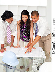 International engineers discussing a construction plan in a...
