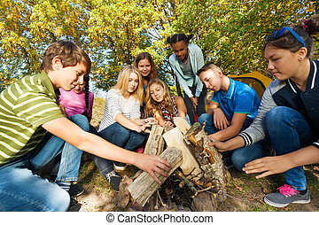 International friends construct bonfire together