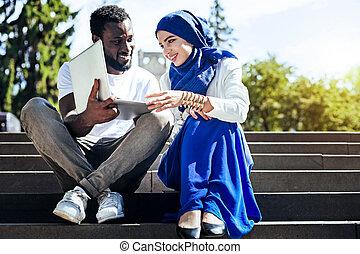 International friends looking at laptop and enjoying pleasant conversation