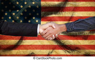 International Handshake with white and dark skinned businessman on background of the USA flag.