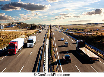 International shipment, trucks and cars driving on the road. Logistics and warehousing