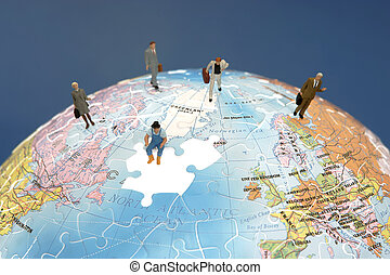 International Teamwork - Business figurines standing on a...