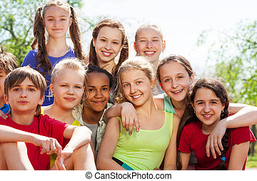International teenagers sitting close in park - ...